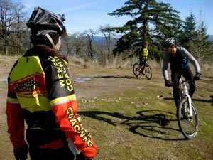 Coach Elaine Bothe teaches at a small group mountain bike lesson as she watches a rider take a turn on a grass field.
