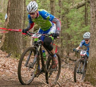 Coach Aaron Oakes climbs on the mountain bike