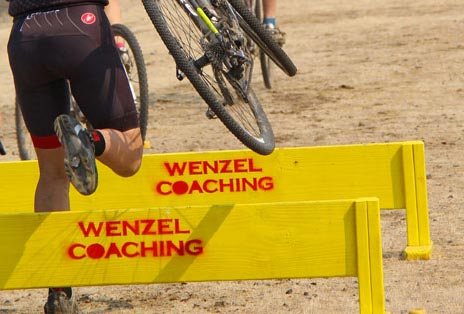 Riders carry their bikes over cyclocross barriers with Wenzel Coaching