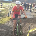 Coach Leia Tyrrell smiles as she rides during a cyclocross race on her mountain bike