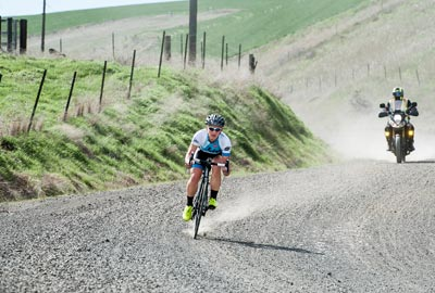 2015 Gorge Gravel Grinder women's winner corners on a gravel road during the race with a race moto following.
