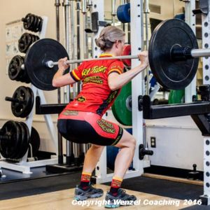 An athlete demonstrates the lower position of the partial squat.