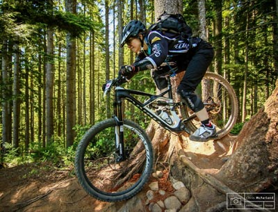Coach Elaine Bothe rides a steep descent on her mountain bike with her weight far behind the saddle