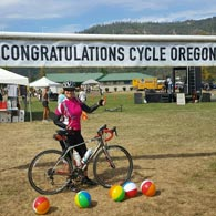 Athlete Amy Coy stands by the welcome banner at the finish of Cycle Oregon 2016, where she rode every segment
