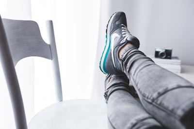 An athlete rests with her legs up on a chair.