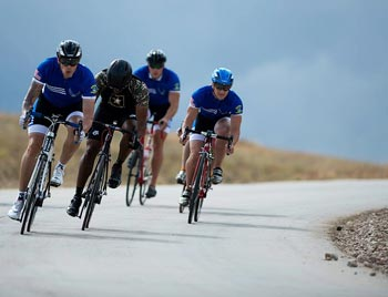 Four cyclists descend on a curved road.
