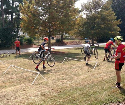 Riders practice carrying their bikes over barriers during a cyclocross clinic