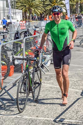 A triathlete runs through the transition area with his bike.