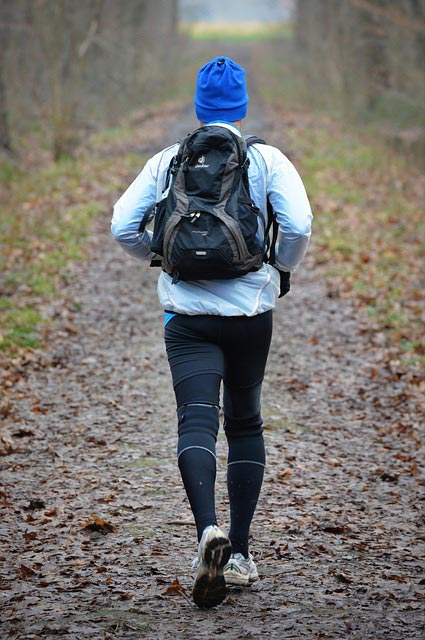 An athlete runs with a backpack on a trail during winter