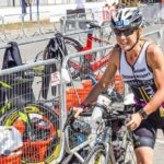 A female athlete runs through a triathlon transition zone.