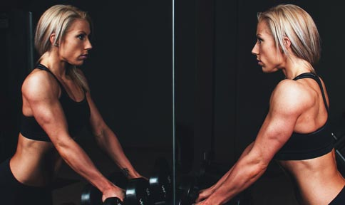 A fit woman looks at herself in a gym mirror.