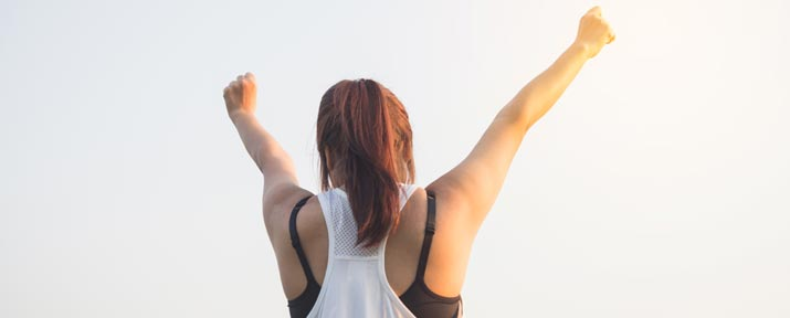A female athlete raises her arms in victory.