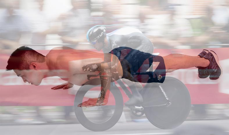 A cyclist time trials while a male athlete holds the plank position.