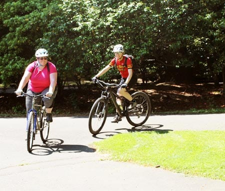 Wenzel Coach Elaine Bothe and a learn-to-ride client ride around a corner in a park.