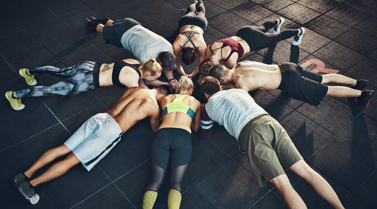 Group holding plank in gym. Flamingo Images, Shutterstock.