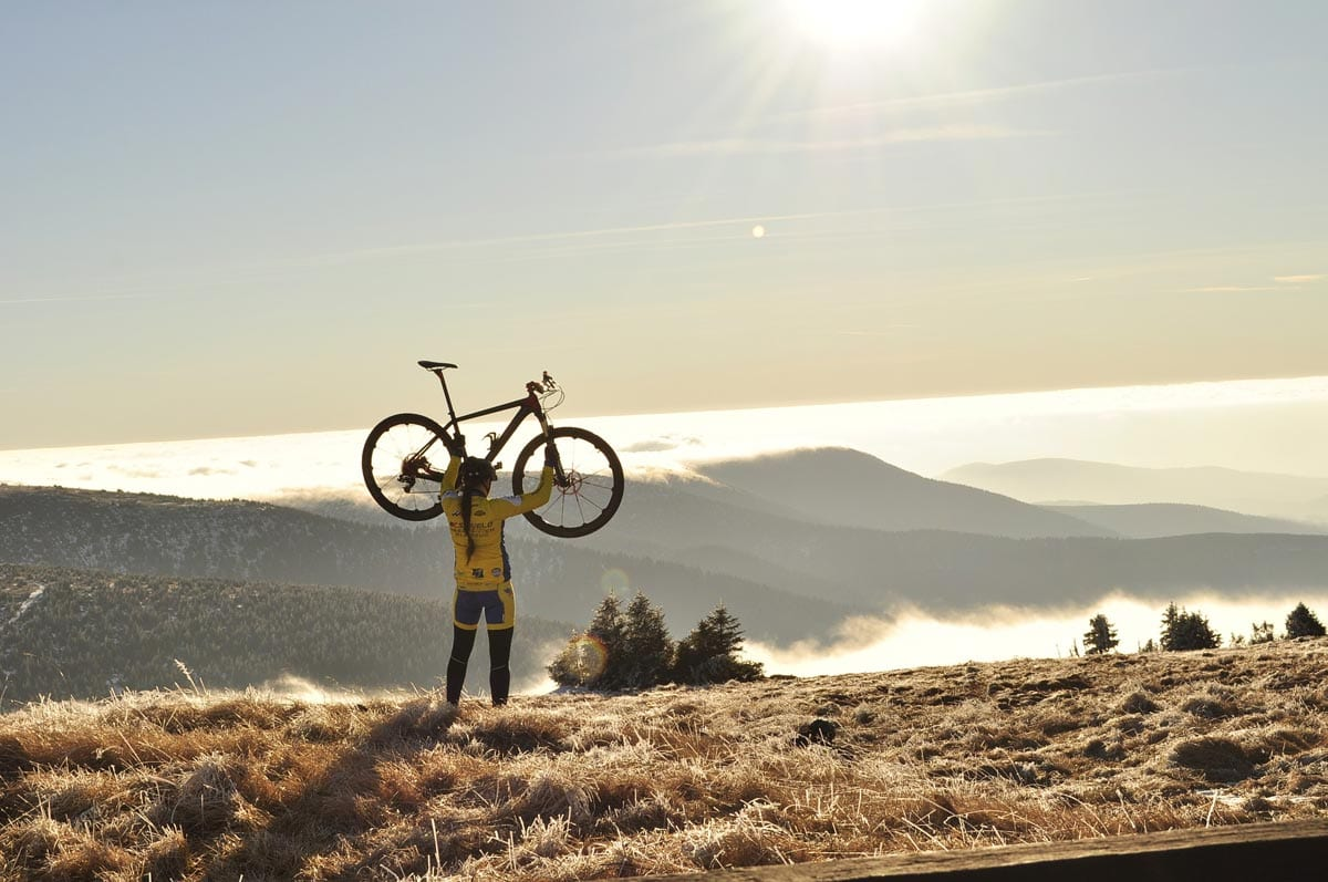 A cyclist holds up her bike in triumph at the top of a climb.