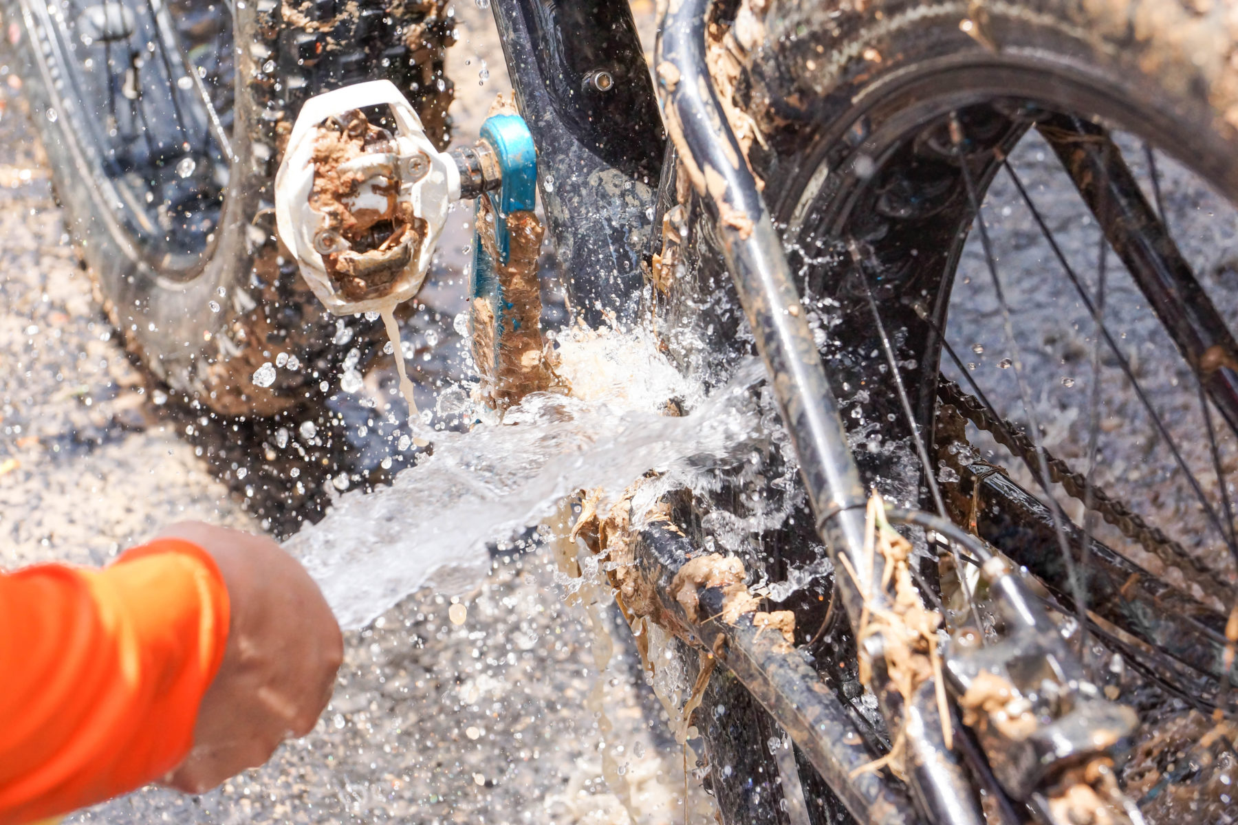 A person aims a hose at a muddy bicycle
