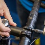 A man checks the handlebar bolts where it meets the stem on the bicycle.
