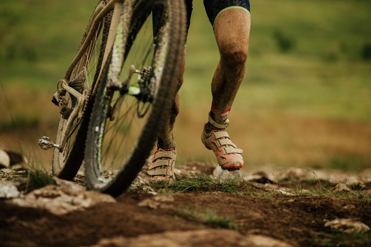 A cyclist pushes a mountain bike over rocks and mud