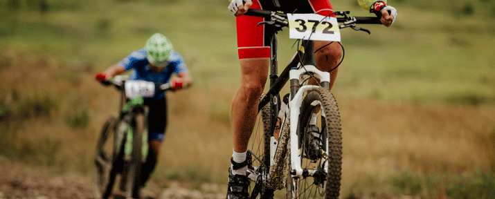 Two riders on mountain bikes tackle a climb. One standing and one off the bike pushing.