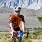 Wenzel Coach Steve Ehasz rides his bike in front of scenic cliffs during an event