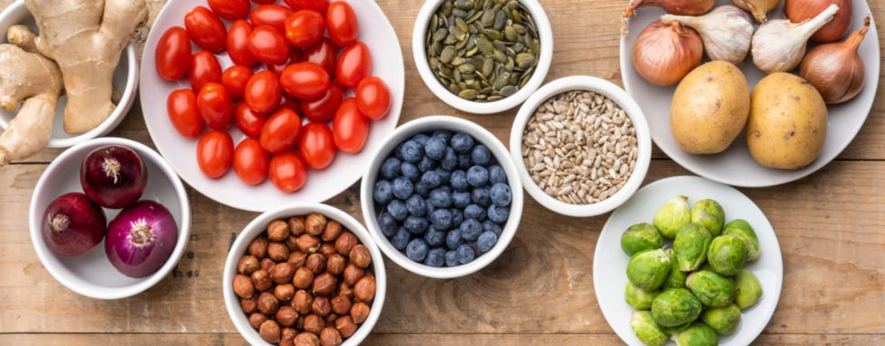 Food that athletes eat, sitting on a table, including nuts, fruits, and vegetables.