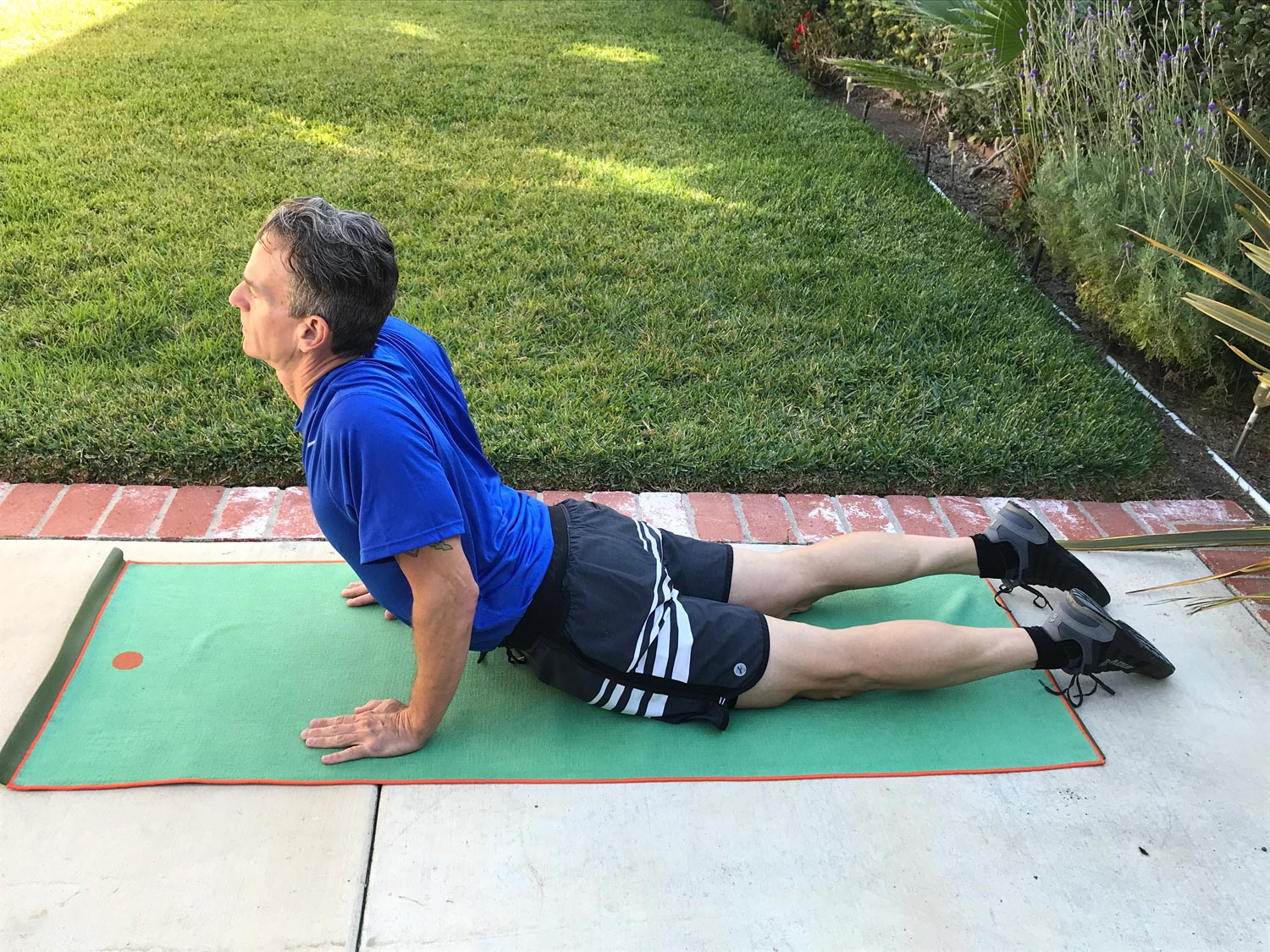 An athlete performs a floor cobra exercise to stretch the hip flexors.