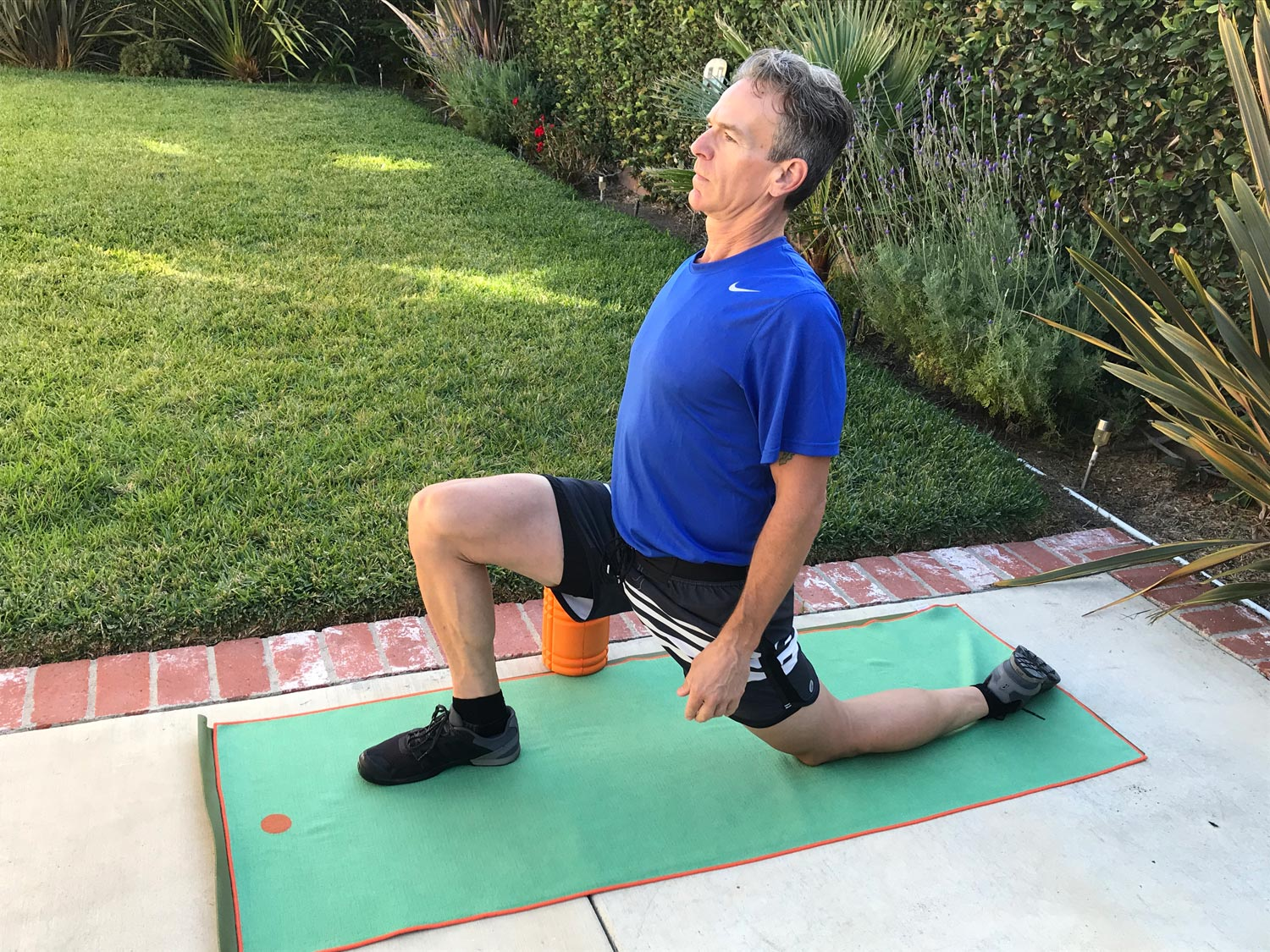 An athlete stretches the hip flexors with one knee kneeling and one on the floor while leaning forward into the stretch.
