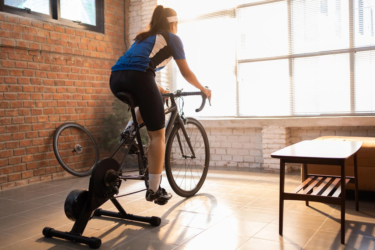 A woman rides indoors on a trainer looking out a bright window