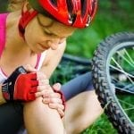 A cyclist sitting on the ground holds her knee in pain